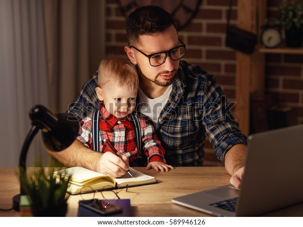 father and son babywork at home at the computer in the dark