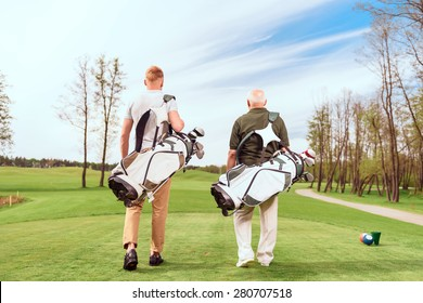 Father and son. Back view of old and young golf players walking on course with golf equipment.