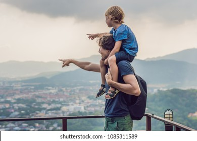 Father and son in the background of Phuket Town view from monkey Hill. Traveling with children concept.