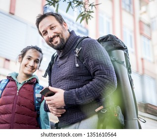 Father and son with backpack traveling in city