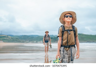 Father and son backpacker travelers walk on sand ocean beach