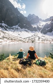 Father and son backpackers resting near the mountain lake Zelene Pleso in Slovakia and enjoying snowy peaks. Spring-summer hiking with kids concept image.