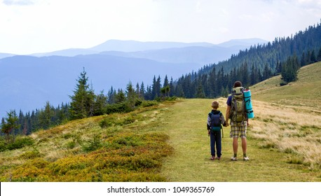 Father and son with backpacks hiking together in scenic summer green mountains. Dad and child standing enjoying landscape mountain view. Active lifestyle, family relations, weekend activity concept.