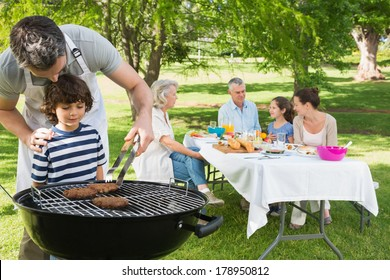 Father and son at barbecue grill with extended family having lunch in the park