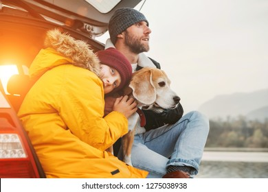 Father and son with beagle dog siting together in car trunk. Late autumn time