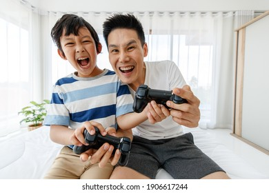 The father and son in bed of the Asian family have fun and happy playing video games on the bed in the room. Concept in a holiday