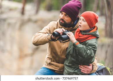 father and son with binoculars spending time together in autumn forest