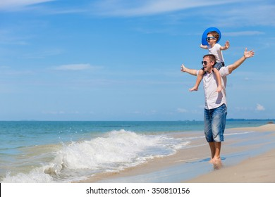 Father and son with blue balloon playing on the beach at the day time. Concept of friendly family.