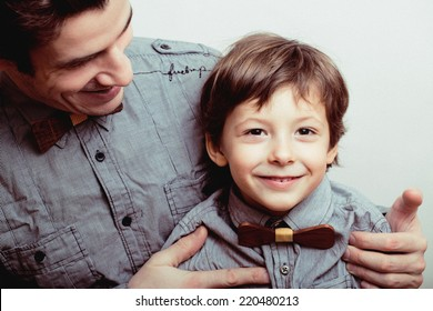 father with son in bowties on white background, casual look family