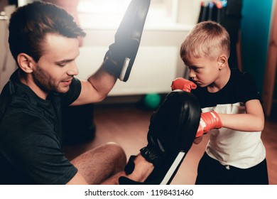 Father And Son Boxing Exercises Training In Gym. Parenthood Relationship. Sporty Family Concept. Active Lifestyle. Kid In Boxing Gloves. Holiday Leisure. Working Out Together. Fitness Day.