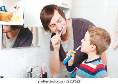 Father and son brushing teeth in bathroom