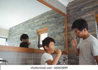Father and son brushing teeth together in bathroom at home