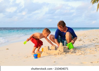 father and son building sandcastle on tropical beach