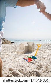 Father and son building sandcastle shaped like house