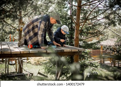 Father and son are building a tree house together. Father is teaching his son to nail. Image with selective focus and toning