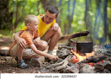Father with son at camping near campfire