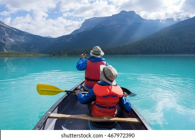 father and son canoeing on Emerald lake early morning with sun rays spilling over the mountains