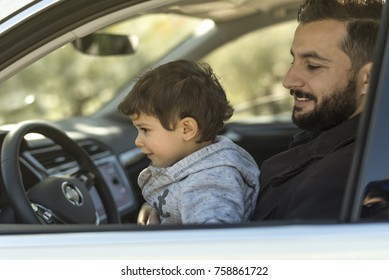 Father and son in car playing driving while are parking waiting