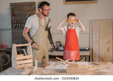 Father and son in the carpenter's home workshop made of wood