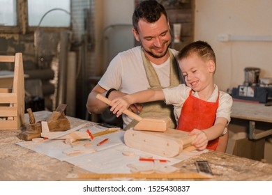 Father and son in the carpenter's home workshop made of wood toys sitting at the table