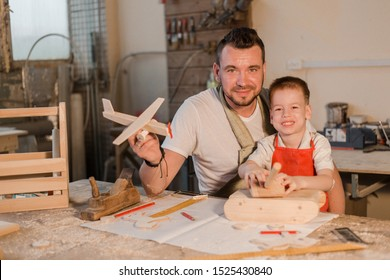 Father and son in the carpenter's home workshop made of wood toys
