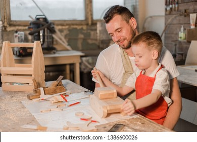 Father and son in the carpenter's shop make a wooden toy tank sitting at the table. Paternal care. Teaching a child craft