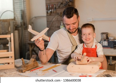 Father and son in the carpenter's shop playing wooden toys airplane and tank made with their own hands. Paternal care. Teaching a child craft
