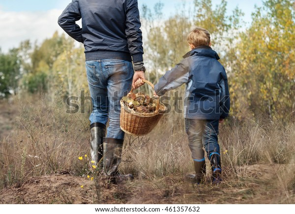 Father and son carry full basket of mushrooms