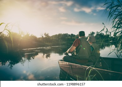father and son catch fish from a boat at sunset, back view wit beautiful lake