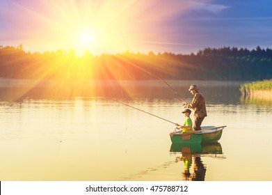father and son catch fish from a boat at sunset