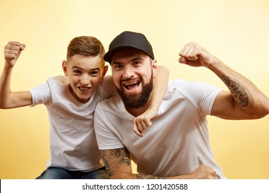Father and son celebrating their success. raised up arms on yellow background
