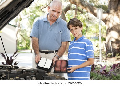 Father and son changing the air filter in the family car.