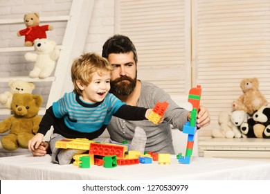 Father and son with cheerful faces create colorful robot out of toy bricks. Family and childhood concept. Man and boy play together. Dad and kid with toys on wooden background build of plastic blocks
