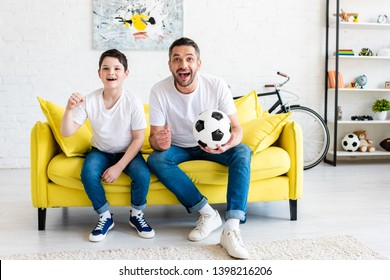 father and son cheering while watching sports match on couch with soccer ball at home