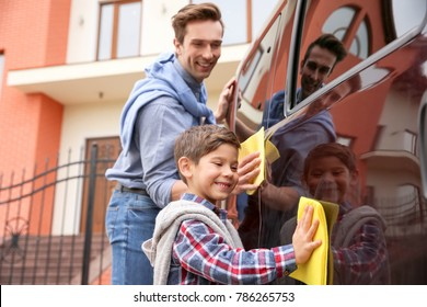 Father and son cleaning car outdoors