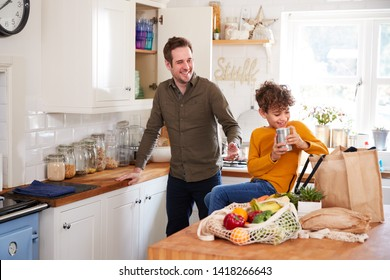 Father And Son Coming Home From Shopping Trip Using Plastic Free Bags Unpacking Groceries In Kitchen
