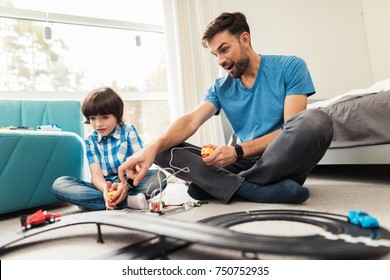 Father and son compete in races with children's cars. They play together on the floor in their house. This is a children's toy.