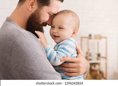 Father and son connection. Dad embracing his adorable baby, closeup portrait