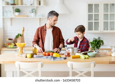 Father and son cooking homemade food together. Dad watching son salting boiled water for spaghetti. Dinner preparation. Fresh products on table. Cozy domestic kitchen interior. Parent child pastime