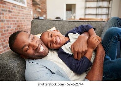 Father And Son Cuddling On Sofa Together