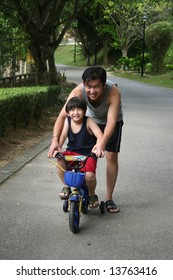 Father and son cycling at the park in the evening