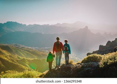 father with son and daughter hiking in mountains