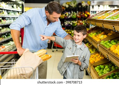 Father and son doing grocery shopping at the supermarket