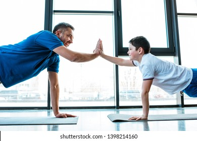 father and son doing high five sign while doing push up exercise at gym