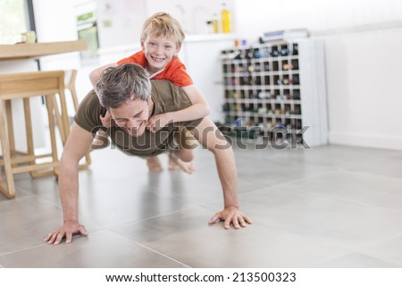 father and son  are doing push ups and having fun  at home