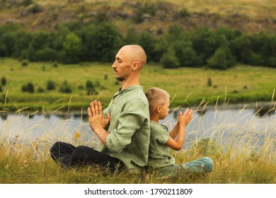 Father and son doing yoga in mountains Beautiful nature scenery Active lifestyle Restart of normal life after the pandemic