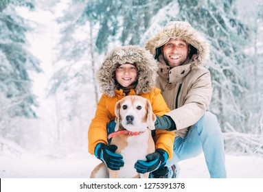 Father and son  dressed in Warm Hooded Casual Parka Jacket Outerwear walking with their beagle dog in snowy forest cheerful smiling faces portrait. Pets in family and winter outfit concept image.