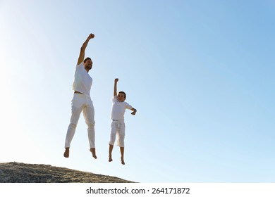 Father and son dressed in white jumping with fist raised in the air on top of a  hill.