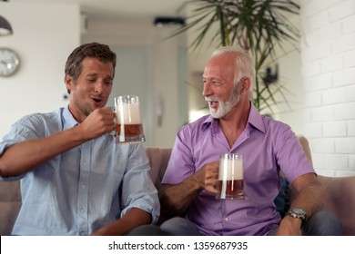 Father and son drink beers and watching football game at home.