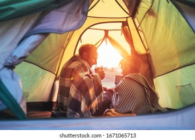 Father and son drink hot tea sitting together in camping tent. Traveling with kids and active people concept image.